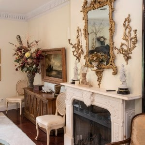 An elegant living room with antiques, ornate white fireplace and gold mirror and decorations