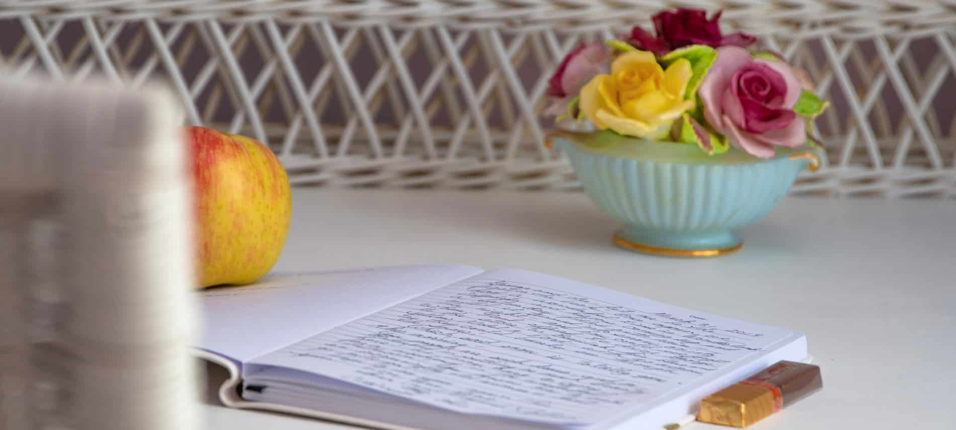 Open journal on a table with a bowl of roses and a piece of chocolate.