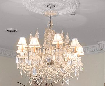 Alrge crystal chandelier with white shades hangs from porcelain medallion.