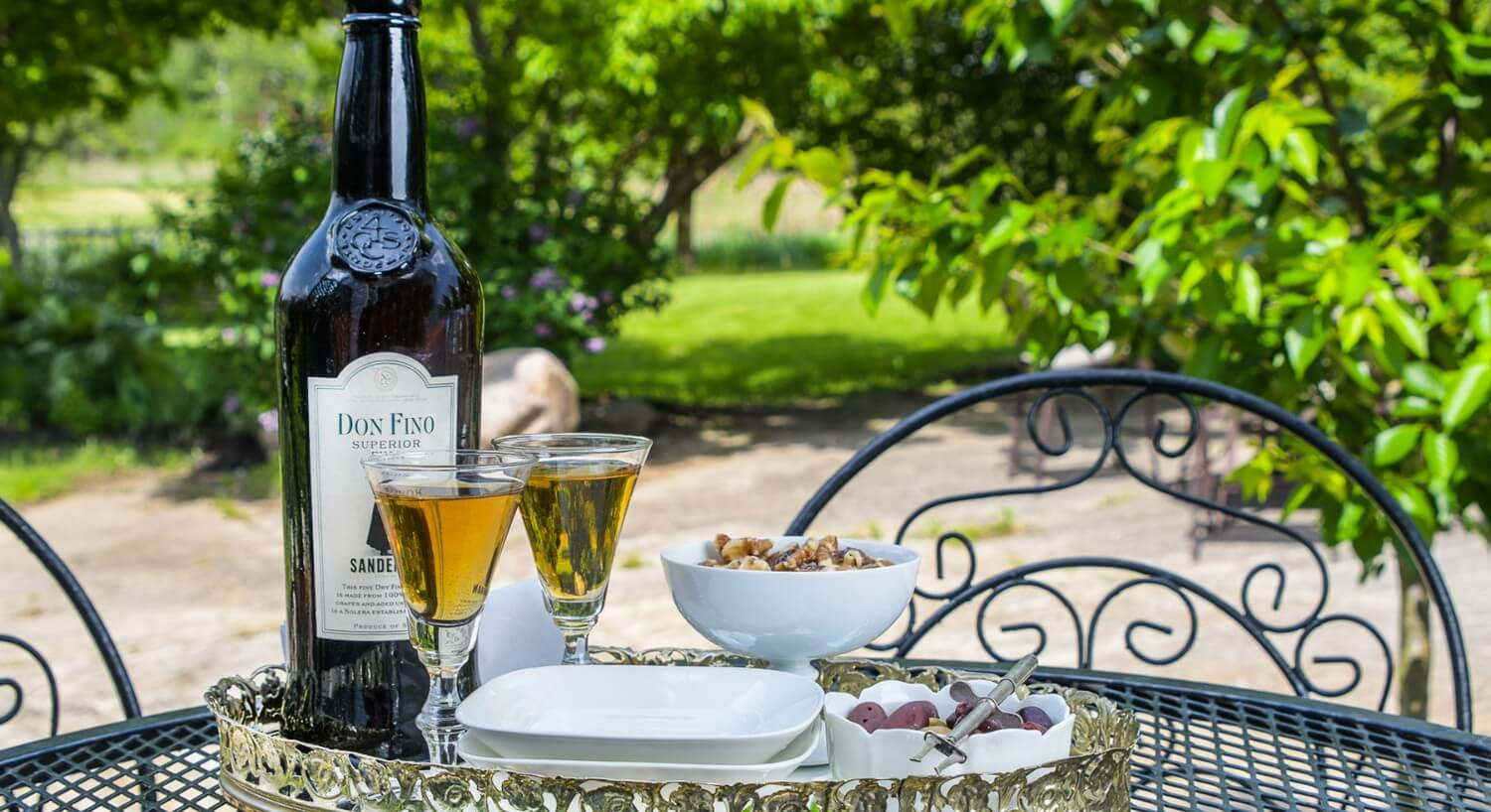 Bottle of liqueur and two glasses on a tray with nuts set on a wrough iron patio table.