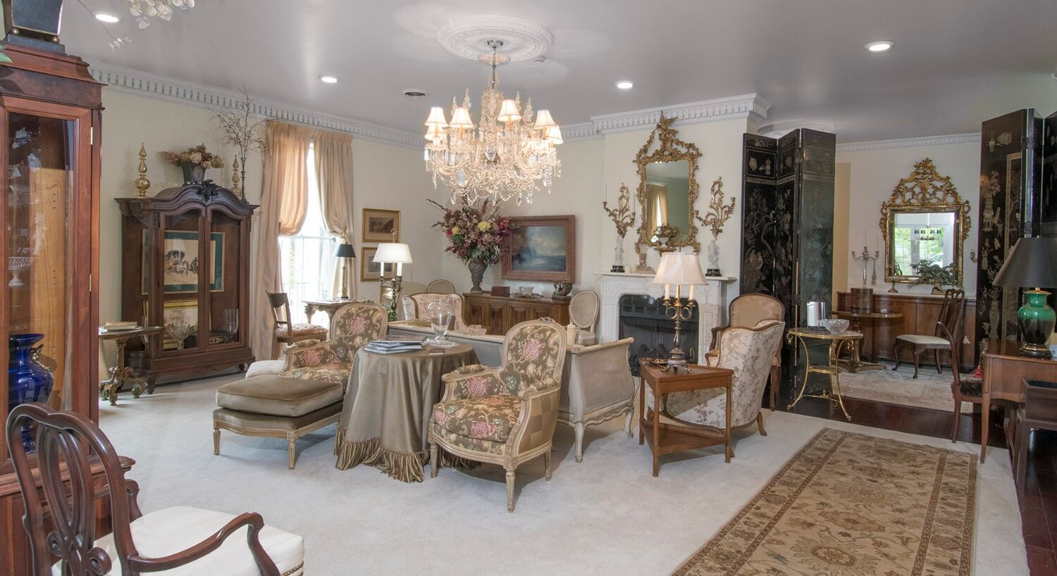 Lavish sitting area with elegant antique furniture, wingback chairs and a fireplace.