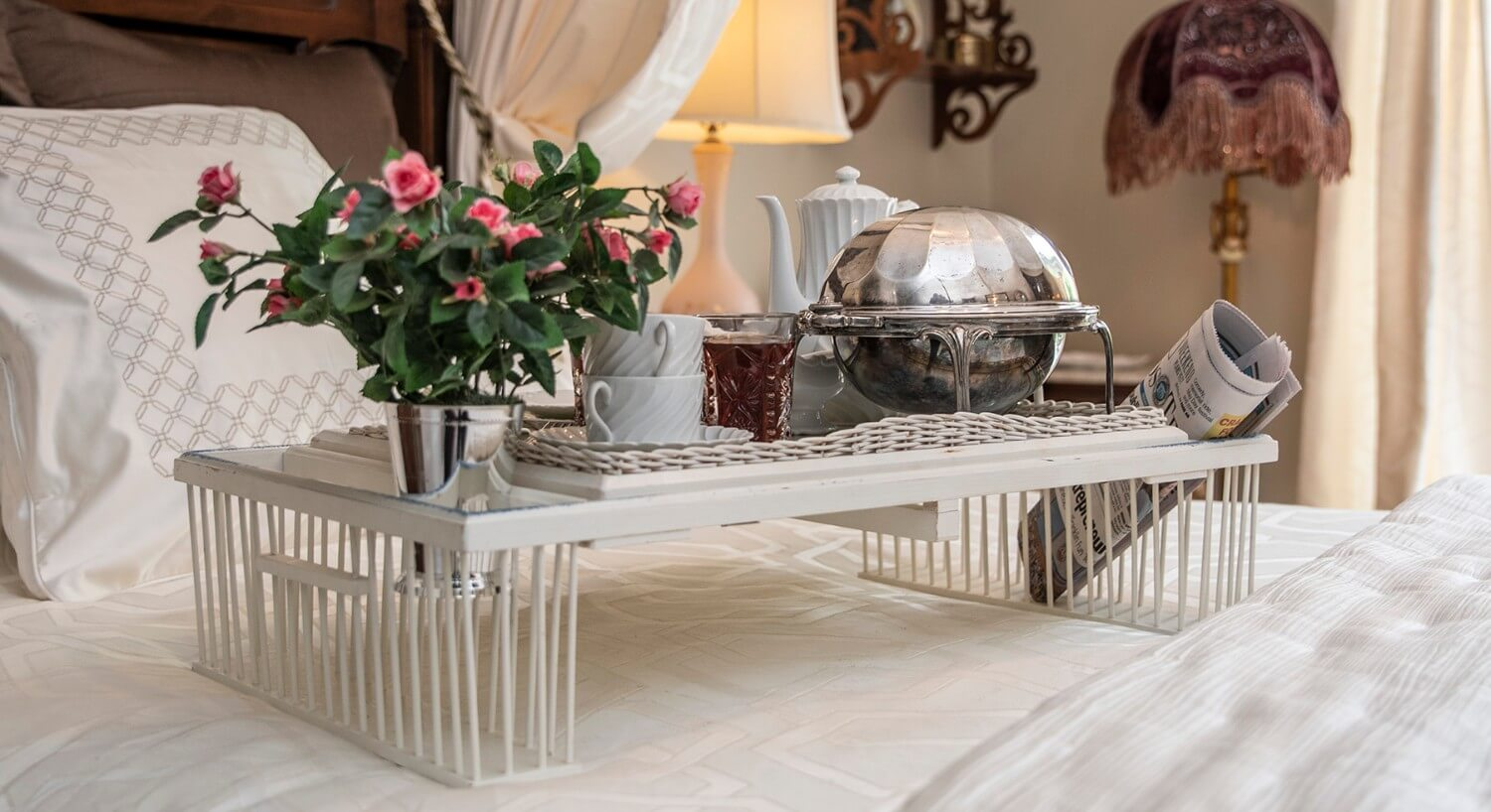 Breakfast tray set with silver and roses on a bed made up in white bedding.