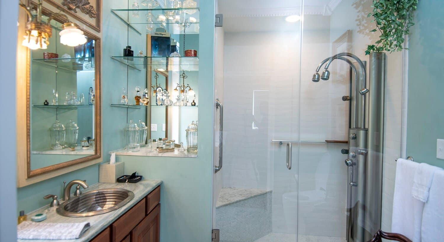 Bright bathroom with glassed-in shower, steel vanity sink and antique decor.