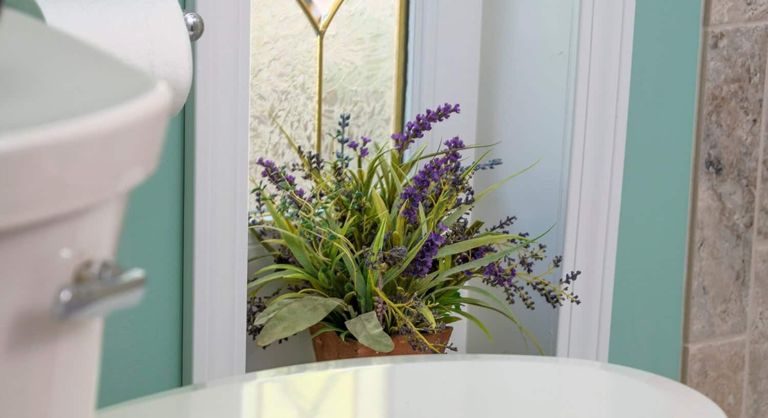 Potted lavender plant in bathroom window.