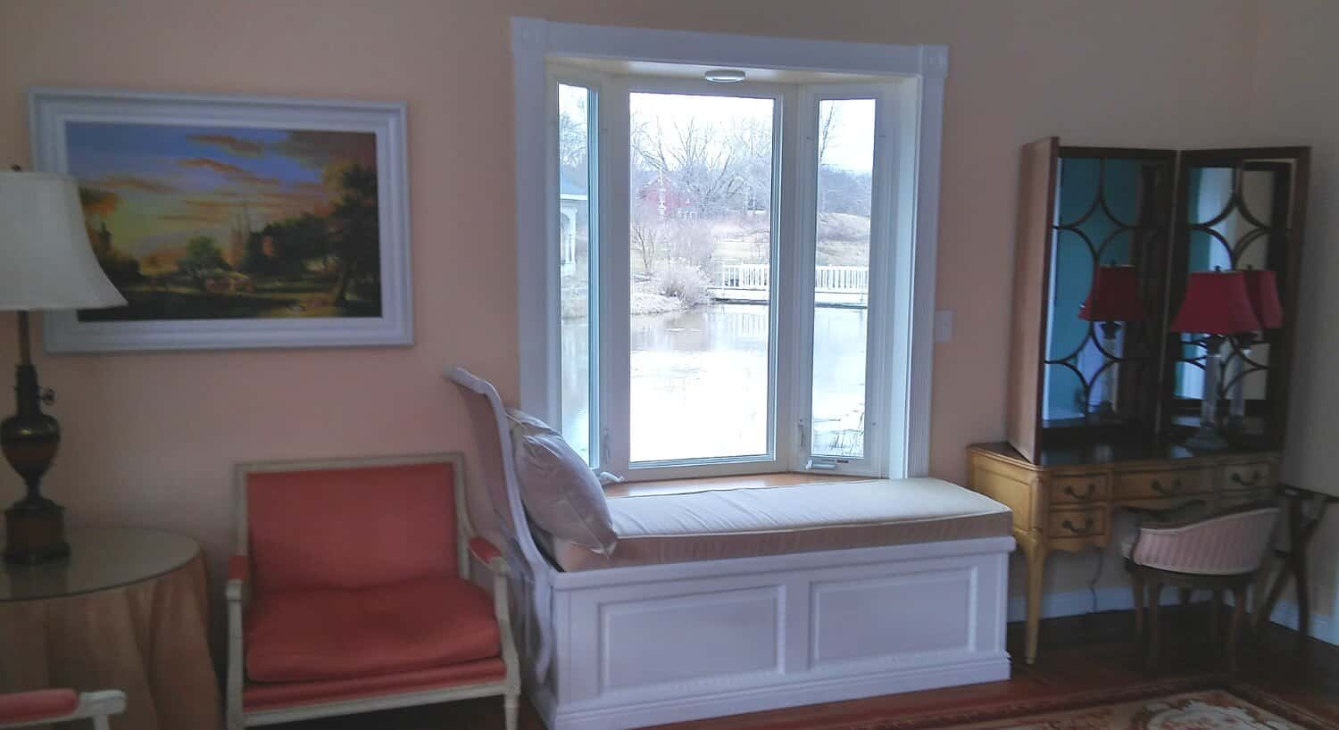 Cozy windowseat in peach room overlooking a pond with a bridge.