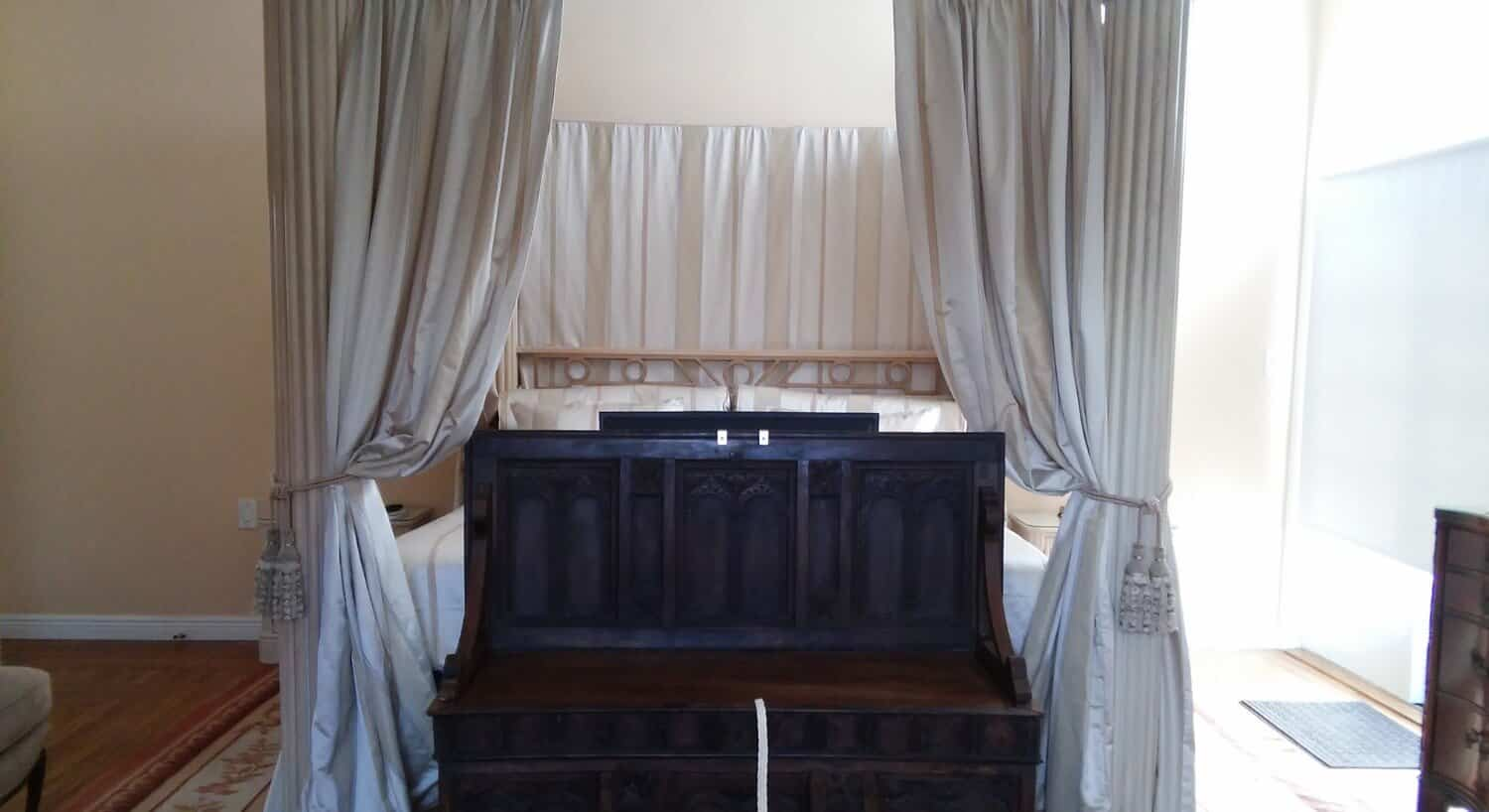 Antique pew at end of a canopy bed made up in heavy silken  bedding.