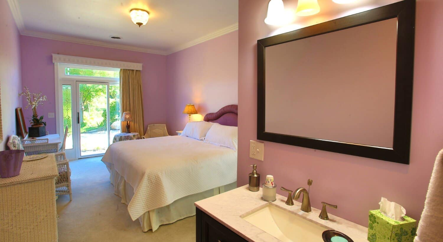 Light filled bedroom with lavender walls and a french door holds a bed with a purple upholstered headboard.