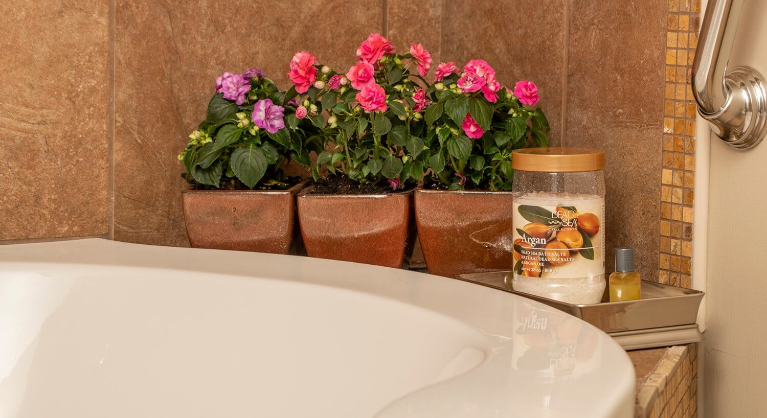 Mini-roses in copper pots sit on the ledge of a soaking tub.