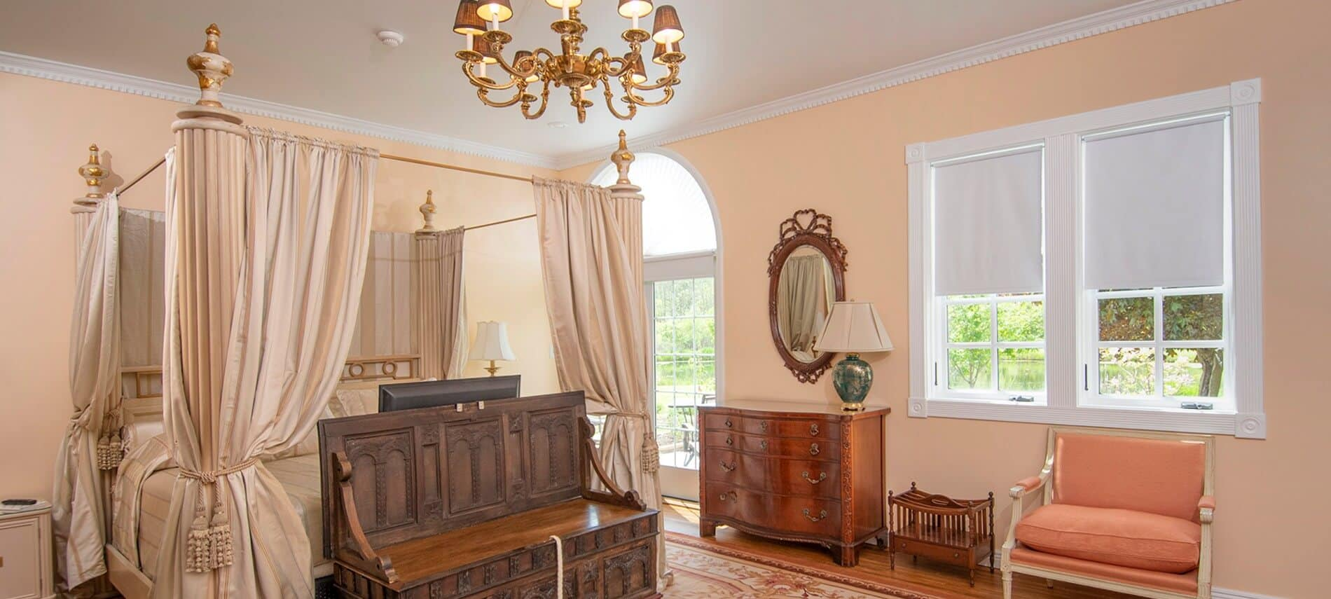 Large and light-filled bedroom with a canopy bed with ivory hangings, gold chandelier and antique dresser.