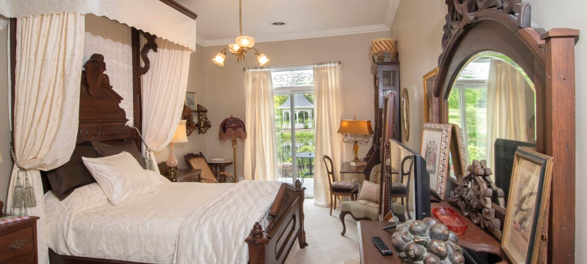 Elegant ivory bedroom holds large antique bed with an antique draped headboard.