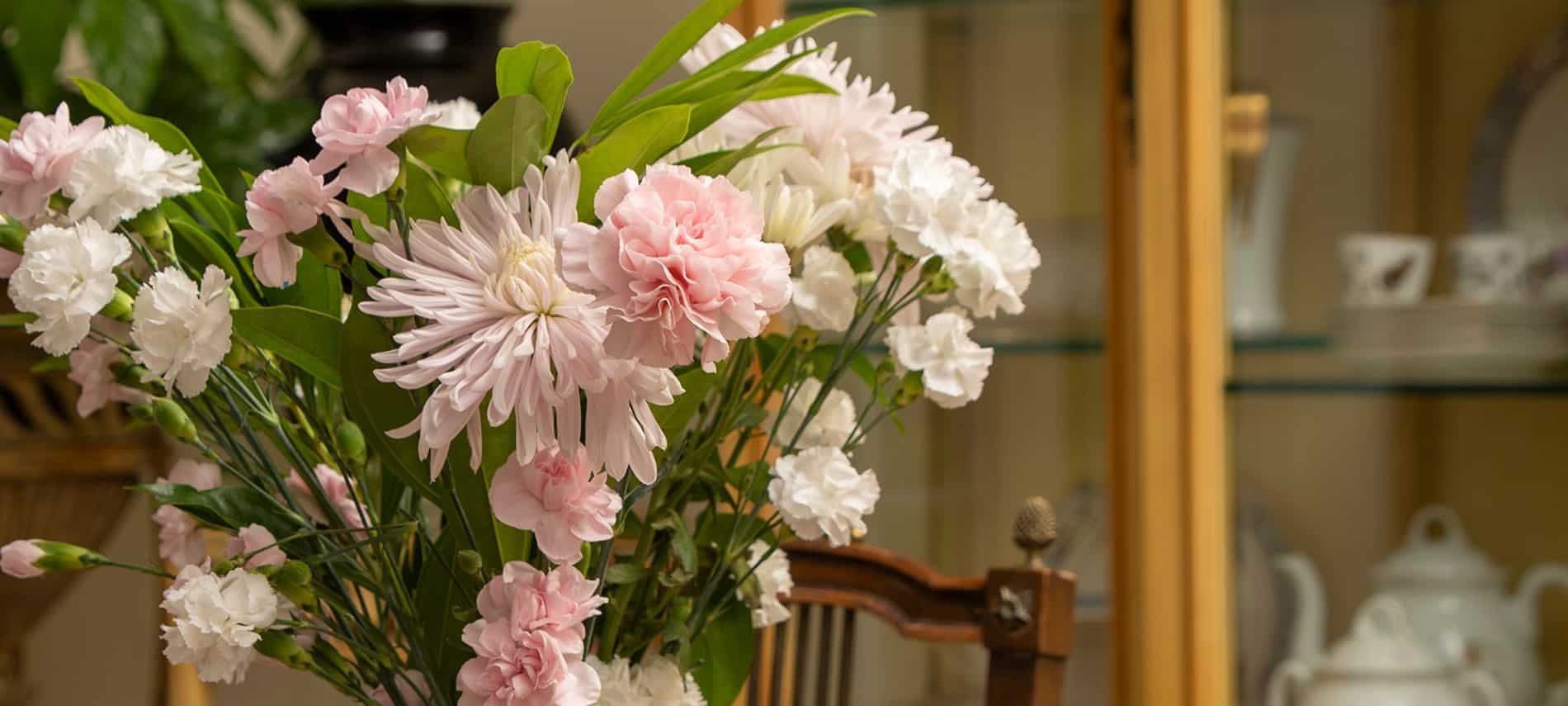 Pink and white mums and carnations in a vase in front of a china cabinet.