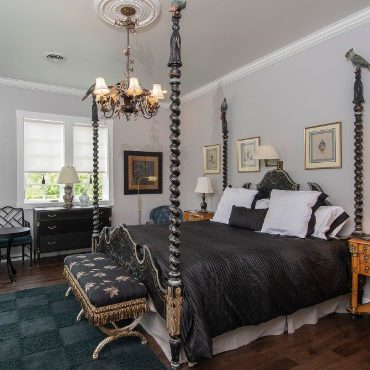 Striking bedroom with unique turned-posts on bed, black bedding and furniture.