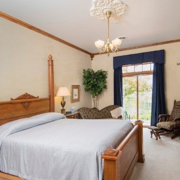 Large wooden four-post bed with white beddign in a room with rocking chair, patio doors and armoire.