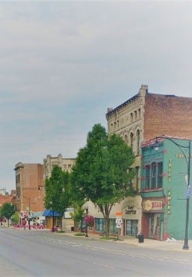 Quaint downtown area with large old brick buildings and green trees.