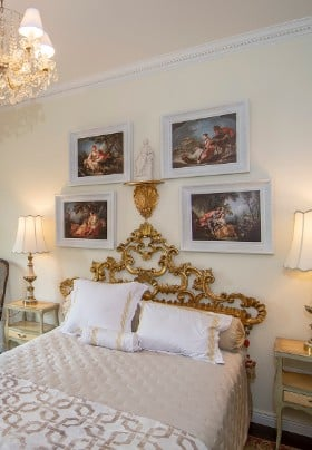 Bed with gold scrolled headboard, gold and ivory bedding, and art prints on walls.
