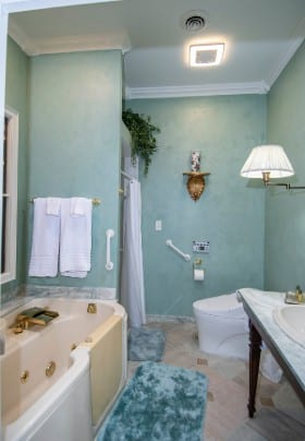 Bathroom with pale green walls, soaking tub, shower and antique wooden vanity table.