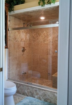 Tiled and glassed-in shower with a built-in seat.
