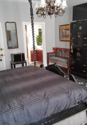 Large four-post bed made up in sikly bedding in a room with antique furniture.