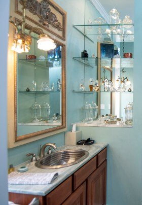 Steel vanity sink in wooden vanity next to glass shelves with antique glass pieces.