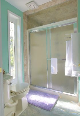 Bright bathroomw with aqua walls and a shower with sliding frosted glass doors.