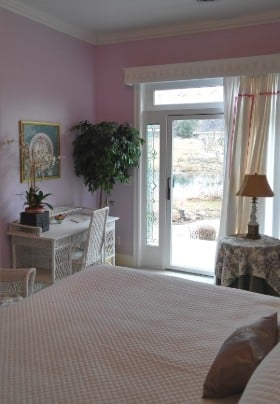 Bedroom view of french door from side of queen bed with white bedding, wicker desk and chair.