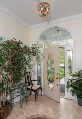 Foyer with tiled floor, chandelier, potted tree and mirrored table.