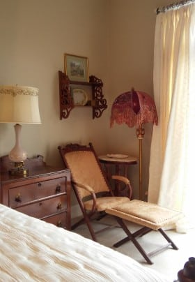 Antique folding chair and footrest in a bedroom with large window and wooden nightstand next to bed.