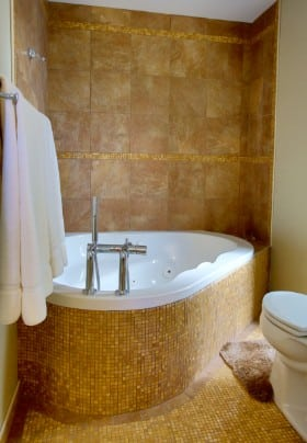 Bathroom tiled in tan with a large soaking tub.