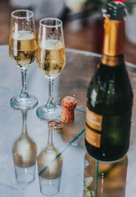 Chilled champagne in flutes next to bottle with a gold label.