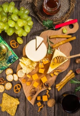 Cheese and grapes on a cutting board with glasses of wine.
